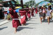 Catholic devotees carry wooden crosses as a form of penance during holy week on April 17 2014 in Pampanga Philippines The brutal practice is a form...