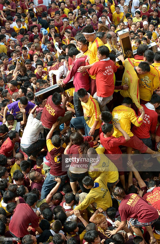 Catholic devotees climb over one another to try to kiss the cross (R) draped on the statue of Black Nazarene during the annual procession in honor of the centuries-old icon of Jesus Christ in Manila on January 9, 2013. Masses of Catholic devotees swept through the Philippine capital on January 9 in a spectacular outpouring of passion for a centuries-old icon of Jesus Christ that many believe can perform miracles. AFP PHOTO / Jay DIRECTO