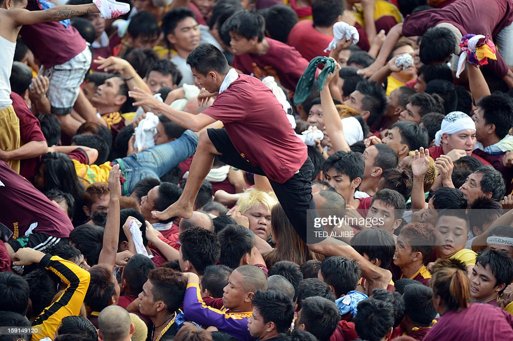 Catholic devotees jostle for position as they try to kiss a cross draped on the life-size statue (not pictured) of the Black Nazarene during the annual procession in honor of the centuries-old icon of Jesus Christ in Manila on January 9, 2013. Masses of Catholic devotees swept through the Philippine capital on January 9, in a spectacular outpouring of passion for a centuries-old icon of Jesus Christ that many believe can perform miracles. AFP PHOTO/TED ALJIBE