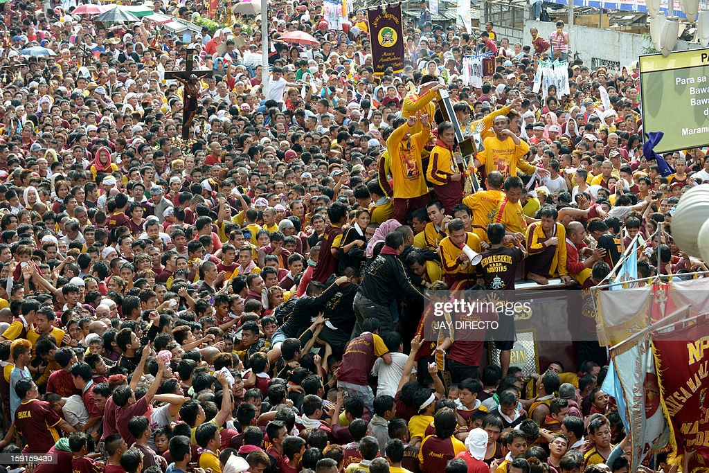 Catholic devotees jostle for positions as they climb over one another to try to kiss the cross (centre R) draped on the statue of Black Nazarene during the annual procession in honor of the centuries-old icon of Jesus Christ in Manila on January 9, 2013. Masses of Catholic devotees swept through the Philippine capital on January 9 in a spectacular outpouring of passion for a centuries-old icon of Jesus Christ that many believe can perform miracles. AFP PHOTO / Jay DIRECTO