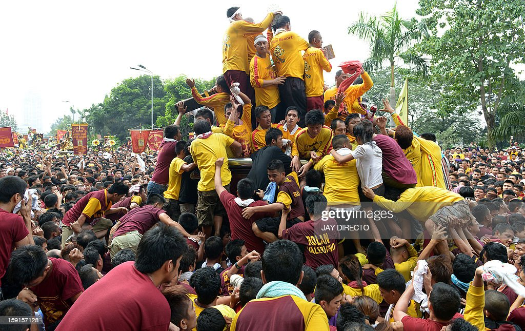 Catholic devotees jostle for positions as they try to kiss the cross (top C) draped on the statue of Black Nazarene during the annual procession in honor of the centuries-old icon of Jesus Christ in Manila on January 9, 2013. Masses of Catholic devotees swept through the Philippine capital on January 9 in a spectacular outpouring of passion for a centuries-old icon of Jesus Christ that many believe can perform miracles. AFP PHOTO / Jay DIRECTO