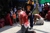 Catholic devotees kneel before a makeshift altar of Christ as a form of penance during holy week on April 17 2014 in Pampanga Philippines The bloody...