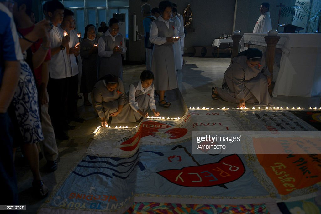 Catholic devotees light candles around quilts made by victims of HIV-AIDS who died of complication because of HIV-AIDS in a church in suburban Manila on December 1, 2013. The Department of Health in the Philippine recorded a total of almost 500 HIV-AIDS cases in October 2013, or 66 percent higher than the 295 cases in October 2012, making it the highest ever recorded in a month in the country. AFP PHOTO / Jay DIRECTO