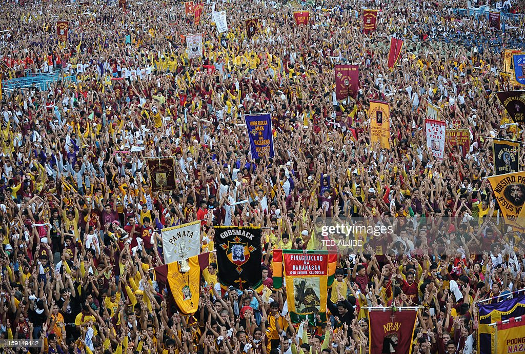 Catholic devotees raise their hands during the annual procession in honor of the centuries-old icon of Jesus Christ, the Black Nazarene (not pictured) in Manila on January 9, 2013. Masses of Catholic devotees swept through the Philippine capital on January 9, in a spectacular outpouring of passion for a centuries-old icon of Jesus Christ that many believe can perform miracles.