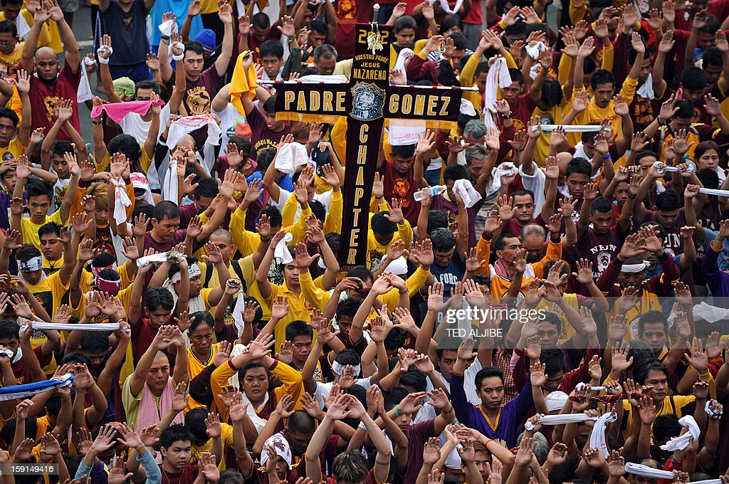 Catholic devotees raise their hands near the life-size statue of the Black Nazarene during the annual procession in honor of the centuries-old icon of Jesus Christ in Manila on January 9, 2013. Masses of Catholic devotees swept through the Philippine capital on January 9, in a spectacular outpouring of passion for a centuries-old icon of Jesus Christ that many believe can perform miracles.