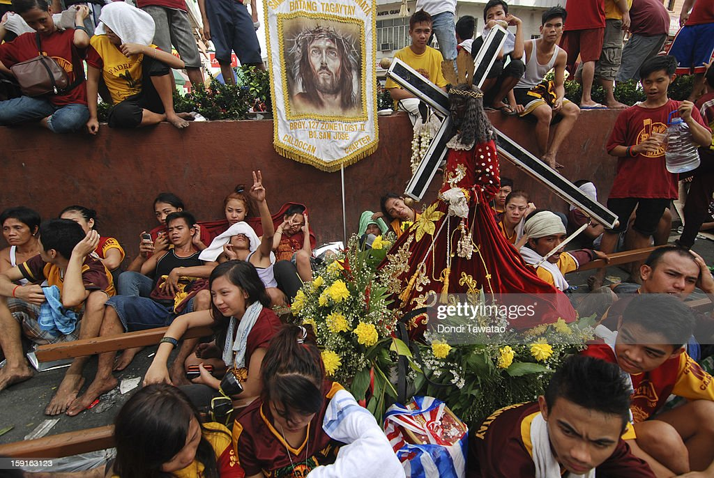Catholic devotees rests from carry a Black Nazarene replica during a parade of millions on the 406th feast of The Black Nazarene on January 9, 2013 in Manila, Philippines. Devotees march barefoot as a sign of sacrifice during the procession as the Black Nazarene is carried in turn through Manila's thouroughfares. The dark wood sculpture of Jesus was brought to the Philippines in the 1600s during the Spanish colonization of the Philippines and is revered by Catholic devotees who claim the statue possess miraculous powers.