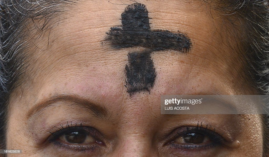 A Catholic faithful has her forehead marked with a cross of ash during the celebration of Ash Wednesday in Bogota on February 13, 2013. Ash Wednesday initiates the Christian period of Lent, that ends in the Holy Week. The ash symbolizes the mortality of human beings. AFP PHOTO/Luis Acosta
