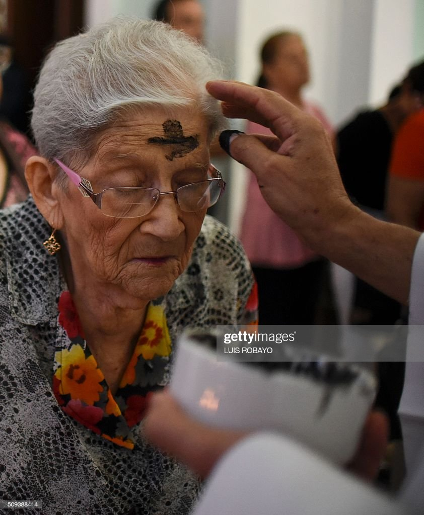 A Catholic faithful participates in a mass for Ash Wednesday on February 10, 2016, in Cali, Colombia. Ash Wednesday marks the beginning of Lent, a period of penitence for Christians before Easter. AFP PHOTO / LUIS ROBAYO / AFP / LUIS ROBAYO