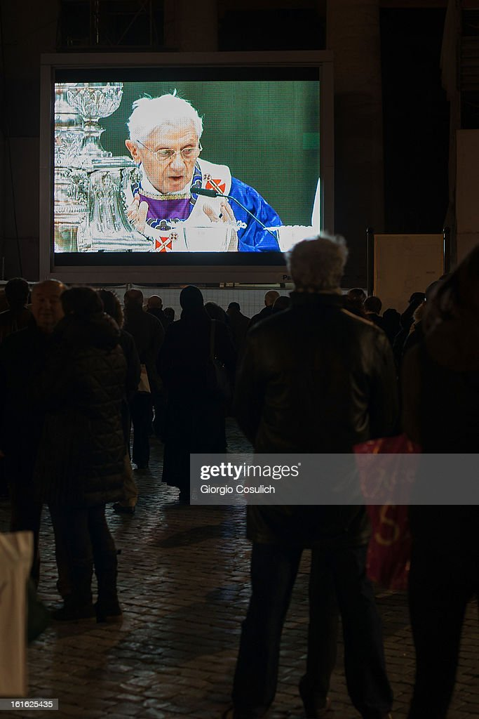 Catholic faithful watch Pope Benedict XVI on a screen in Saint Peters' Square as they attend the celebration of the Ash Wednesday mass on February 13, 2013 in Vatican City, Vatican. The Pontiff will hold his last weekly public audience on February 27 at St Peter's Square after announcing his resignation earlier this week.
