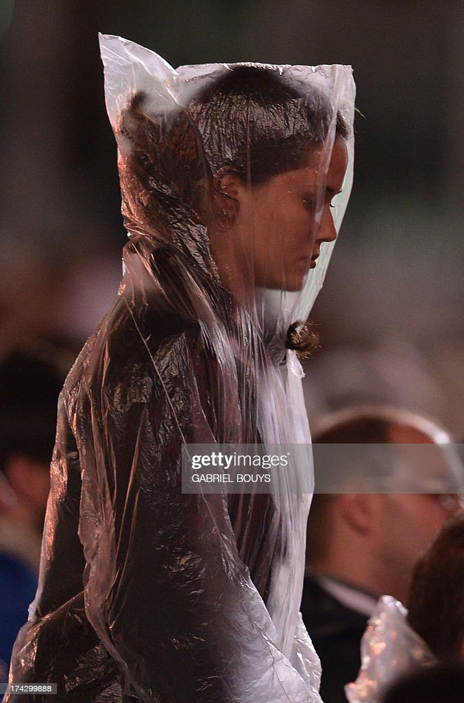 A Catholic faithful wears a nylon raincoat during the World Youth Day (WYD) opening mass, at Copacabana beach in Rio de Janeiro, Brazil, on July 23, 2013. The highlight of the landmark visit of Pope Francis to the world's most populous mainly Catholic country will be WYD, a five-day event that kicks off today. Pope Francis's popularity on his Latin American home turf posed a challenge to Brazilian authorities Tuesday after adoring crowds mobbed his car on his arrival on Monday. AFP PHOTO / GABRIEL BOUYS