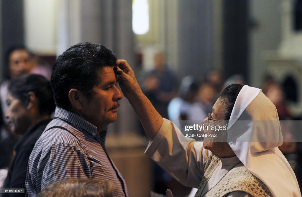 Catholic faithfuls participate in a mass during the celebration of Ash Wednesday in El Calvario parish in San Salvador, El Salvador on February 13, 2013. Ash Wednesday marks the Christian period of Lent, prior to the Holy Week. AFP PHOTO/ Jose CABEZAS