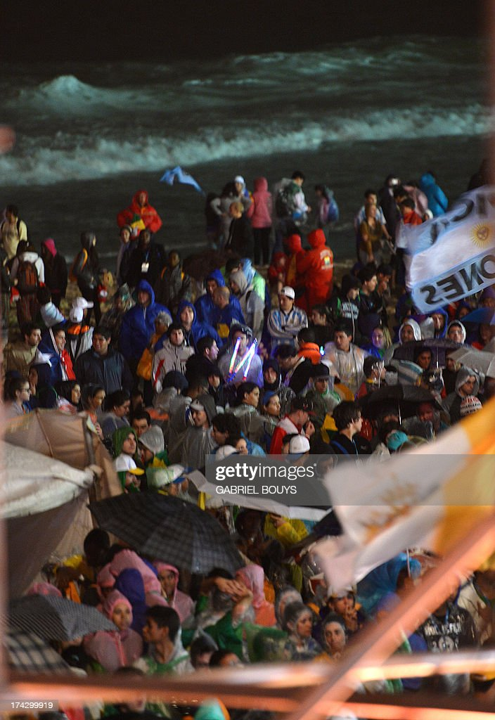 Catholic faithfuls stand next to the shore of Copacabana beach during the World Youth Day (WYD) opening mass, in Rio de Janeiro, Brazil, on July 23, 2013. The highlight of the landmark visit of Pope Francis to the world's most populous mainly Catholic country will be WYD, a five-day event that kicks off today. Pope Francis's popularity on his Latin American home turf posed a challenge to Brazilian authorities Tuesday after adoring crowds mobbed his car on his arrival on Monday.