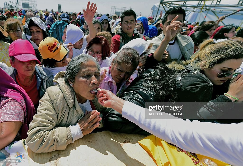 Catholic faithfuls take communion during an open-air mass by Pope Francis in Ecatepec --a rough, crime-plagued Mexico City suburb-- on February 14, 2016. Pope Francis has chosen to visit some of Mexico's most troubled regions during his five-day trip to the world's second most populous Catholic country. AFP PHOTO / ALFREDO ESTRELLA / AFP / ALFREDO ESTRELLA
