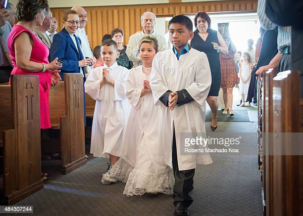 Catholic First Communion Children walk the aisle at first holy communion ceremony Two boys and a girl are all dressed in white robes Family and...