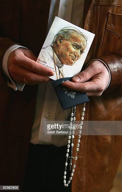 Catholic holds a picture of Pope John Paul II and rosary beads as he prays in honour of the Pontiff in Westminister Cathedral on April 3 2005 in...