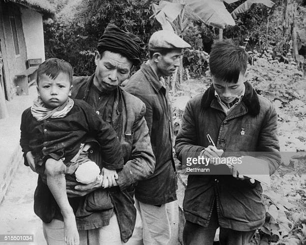 A Catholic Lay Leader of this village holds his son who he reports lost a leg in a U S Raid Bombs also killed the boy's mother and all but one of his...