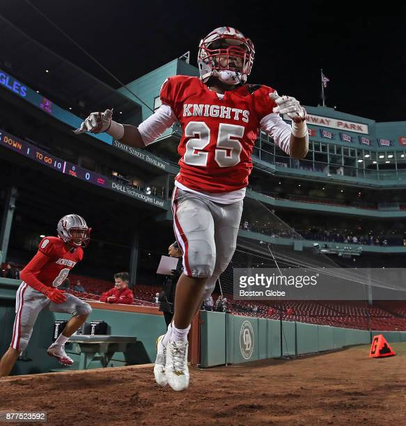 Catholic Memorial's Jamall Griffin and his teammates come out of the Red Sox dugout as they take the field for the start of the game Boston College...