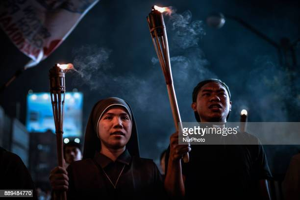A catholic nun and priest hold up torches as they take part in Human Rights Day protests in Manila Philippines December 10 2017 On International...