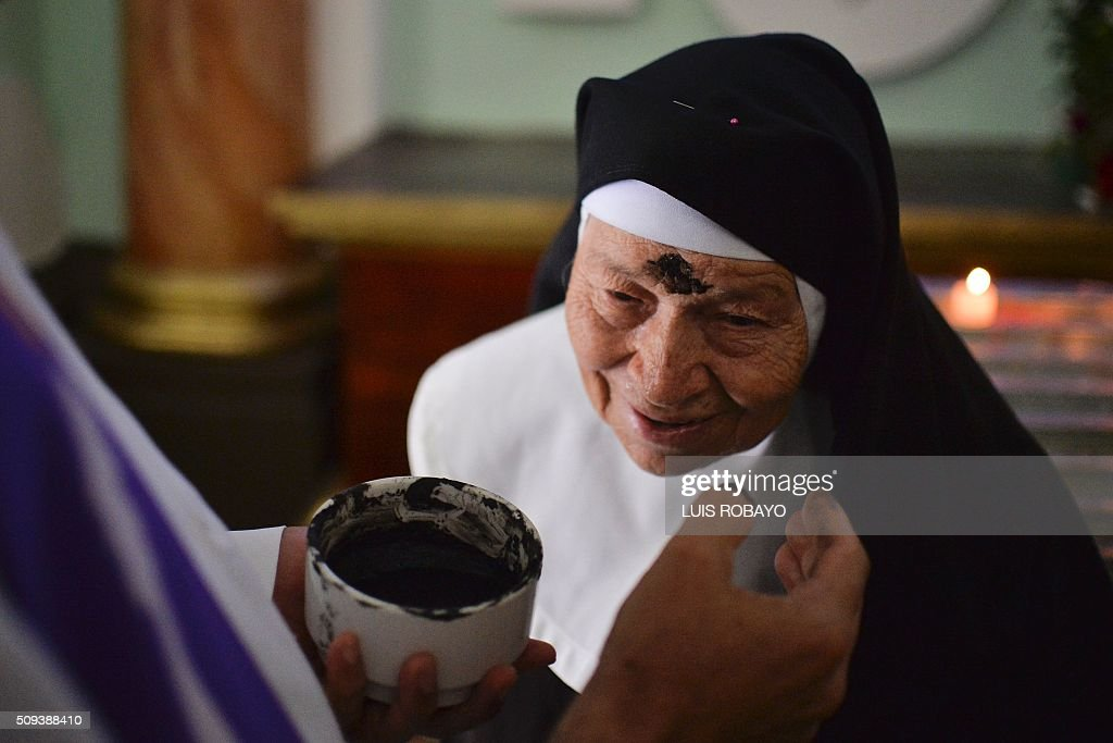 A Catholic nun participates in a mass for Ash Wednesday on February 10, 2016, in Cali, Colombia. Ash Wednesday marks the beginning of Lent, a period of penitence for Christians before Easter. AFP PHOTO / LUIS ROBAYO / AFP / LUIS ROBAYO