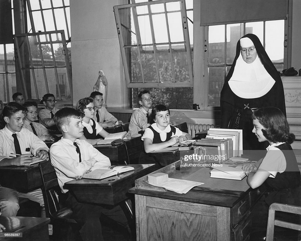 Catholic nun Sister Mary Zita looks on as class president Susan presides over a class meeting at St Mary of the Lake School Chicago Illinois circa...