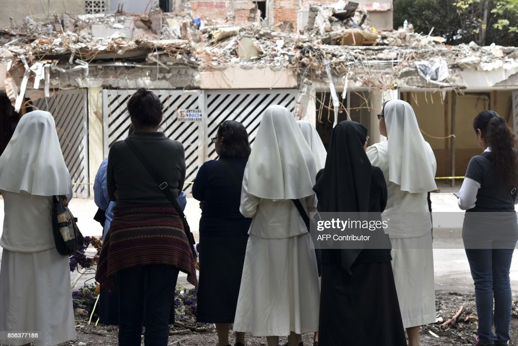 TOPSHOT - Catholic nuns pray in front of one of the buildings crushed during the September 19 earthquake in Mexico City, on October 1, 2017. More than a week after an earthquake that killed over 300 people, a shaken Mexico was torn between trying to get back to normal and keeping up an increasingly hopeless search for survivors. /