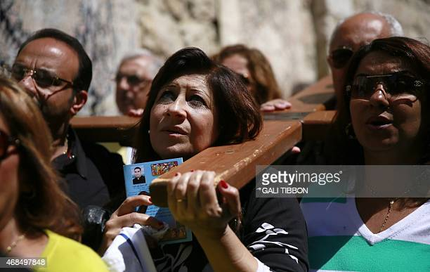 Catholic pilgrims carry a wooden cross along the Via Dolorosa in Jerusalem's Old City during the Good Friday procession on April 3 2015 Many...
