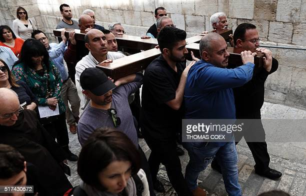 Catholic pilgrims carry a wooden cross along the Via Dolorosa in Jerusalems Old City during the Good Friday procession on March 25 2016 Many...