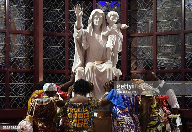 TOPSHOT Catholic pilgrims pray next to a statue of the Virgin Mary at the Our Lady of the Peace basilica in Yamoussoukro on May 21 2016 200000...