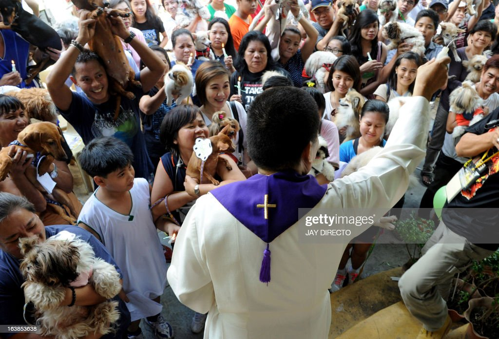 A Catholic priest (C) blesses people's pet dogs and cats with holy water in Manila on March 17, 2013. A local government is offering free veterinary services and free vaccinations against rabies as the Department of Health designated March as Rabies Awareness Month as part of its national rabies prevention and control program, with the aid of eliminating the disease from the Philippines by 2020.