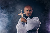 Catholic priest exorcist in white surplice and black shirt with cleric collar praying with crucifix