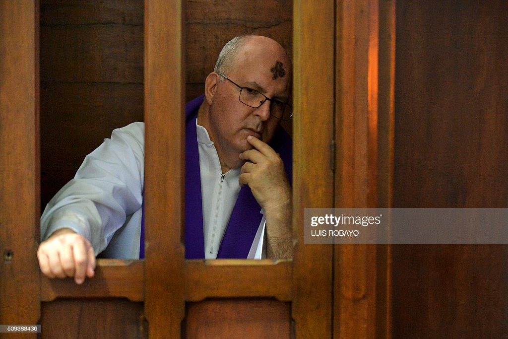 A Catholic priest hears confessiuons from faithful during Ash Wednesday on February 10, 2016, in Cali, Colombia. Ash Wednesday marks the beginning of Lent, a period of penitence for Christians before Easter. AFP PHOTO / LUIS ROBAYO / AFP / LUIS ROBAYO
