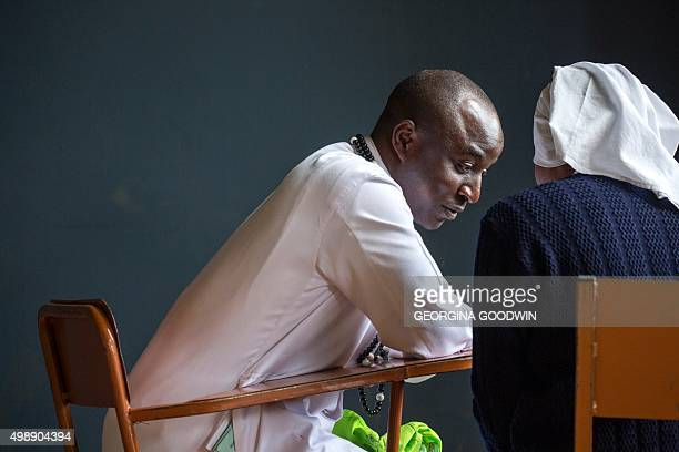 A Catholic priest hears the confession of a nun as people gather at the Kasarani Sport Stadium in Nairobi on November 27 to hear an address by Pope...