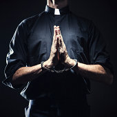 Catholic Priest Praying in Handcuffs