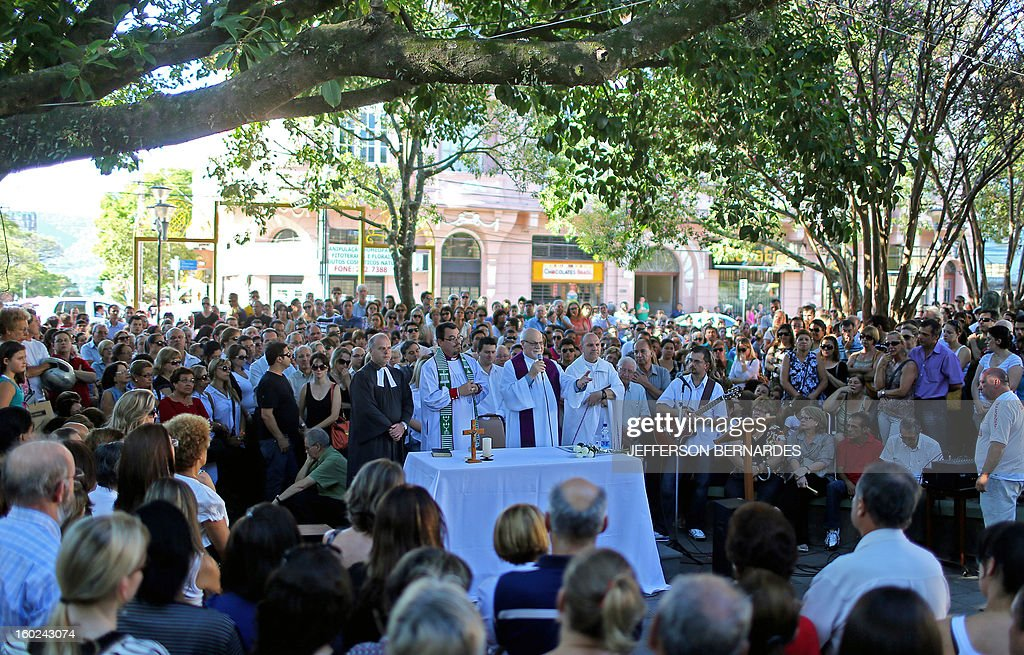 A Catholic priest says mass in a public square in the center of Santa Maria, on January 28, 2013, in Santa Maria, in southern Brazil, where a blaze on the eve killed more than 230 people. Brazilian police arrested four suspects --two of the Kiss club's owners, along with a pair of musicians who starred in the ill-fated pyrotechnic show, in the wake of the nightclub fire that forced sports officials to defend preparations for the World Cup and Olympics.