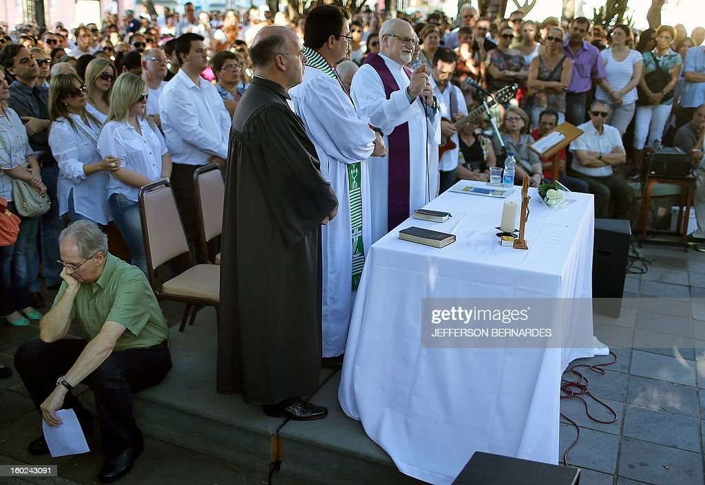 A Catholic priest says mass in a public square in the center of Santa Maria, in southern Brazil, on January 28, 2013, where on the eve a blaze in a nightclub killed more than 230 people. Brazilian police arrested four suspects --two of the Kiss club's owners, along with a pair of musicians who starred in the ill-fated pyrotechnic show, in the wake of the nightclub fire that forced sports officials to defend preparations for the World Cup and Olympics.