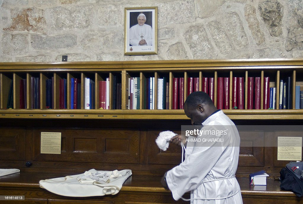 A Catholic priest stands under a portrait of Pope Benedict XVI displayed at the Church of the Holy Sepulcher in Jerusalem's Old City, on February 13, 2013. The Catholic Church faced a tricky transition as it prepared to elect a new pope, with many faithful still reeling from the shock resignation of Pope Benedict XVI.