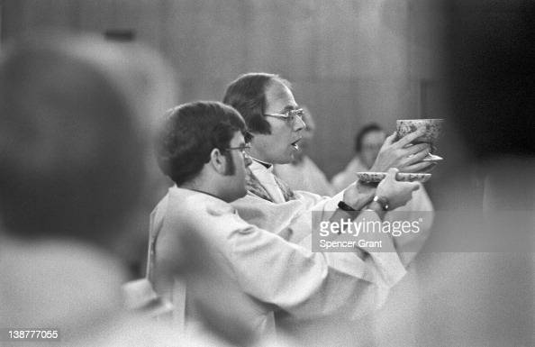 Catholic priests consecrate the bread and wine during a Mass at Boston College in Chestnut Hill Boston Massachusetts 1970