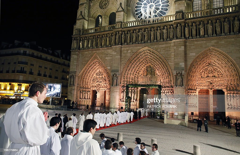 Catholic priests line up to enter 'Notre-Dame de Paris' cathedral, on December 12, 2012 in Paris, as part of its 850th anniversary. Cardinal Andre Vingt-Trois, the archbishop of Paris led a Pontifical Mass in Notre Dame (Our Lady), the iconic cathedral at the heart of the French capital and a masterpiece of Gothic art, which launched from December 12 a year of celebrations to mark the 850th anniversary of its founding. AFP PHOTO PATRICK KOVARIK