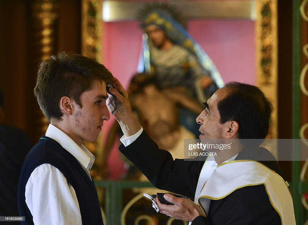 A Catholic priests marks with a cross of ash the forehead of a believer during the celebration of Ash Wednesday in Bogota on February 13, 2013. Ash Wednesday initiates the Christian period of Lent, that ends in the Holy Week. The ash symbolizes the mortality of human beings. AFP PHOTO/Luis Acosta