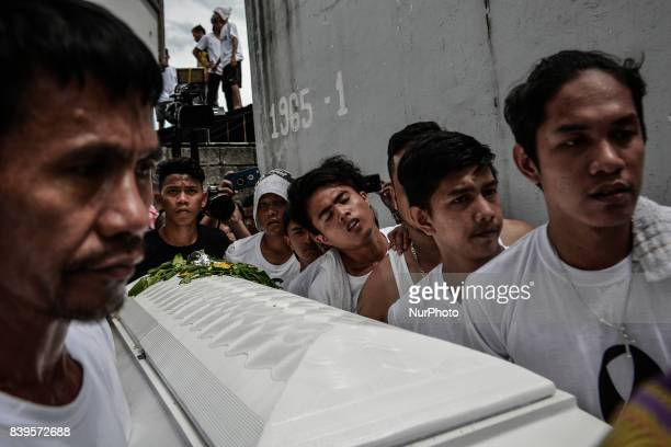 Catholic priests relatives and friends carry the coffin of Kian Loyd Delos Santos during his funeral rites in Caloocan Metro Manila Philippines...