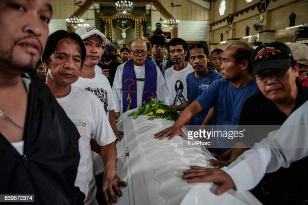 Catholic priests relatives and friends push the coffin of Kian Loyd Delos Santos during his funeral rites in Caloocan Metro Manila Philippines August...