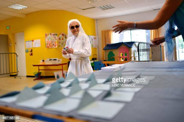 Catholic Sister arrives to vote at a polling station in Nantes western France during the second round of the French parliamentary elections on June...