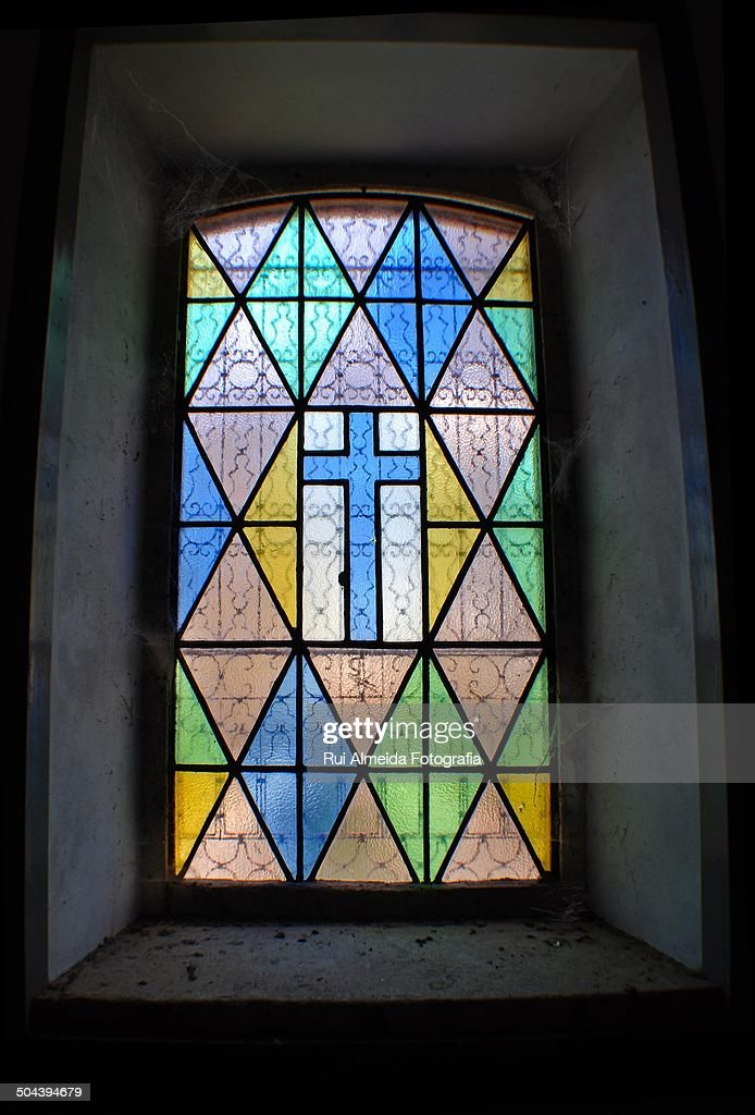 Catholic stained glass cross in dusty church