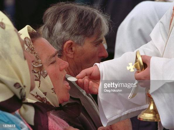 Catholic Ukrainian woman receives Communion from a priest June 24 2001 during an openair Mass held by Pope John Paul II at Chaika airfield on the...