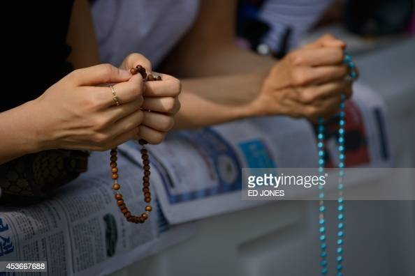 Catholic worshippers hold prayer beads as they attend a mass lead by Pope Francis at Gwanghwamun Square in central Seoul on August 16 2014 Pope...