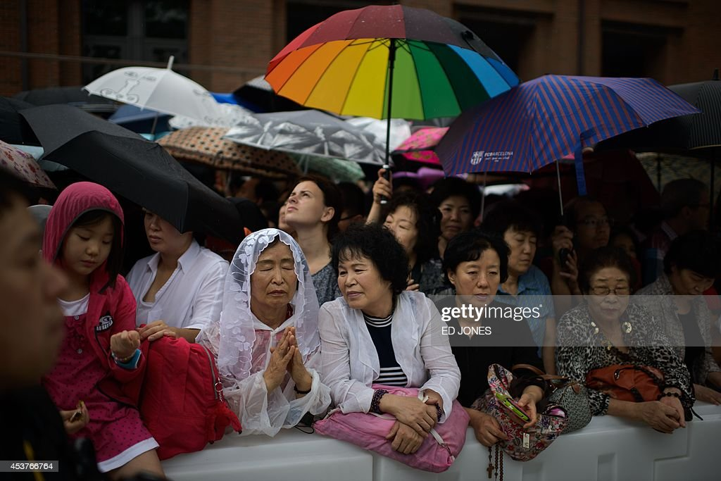 Catholic worshippers outside Myeongdong cathedral during a mass by Pope Francis, in Seoul on August 18, 2014. Pope Francis wrapped up the first papal visit to Asia in 15 years, urging the divided Koreas to reject suspicion and confrontation and unite as 'one family, one people'. AFP PHOTO / Ed Jones