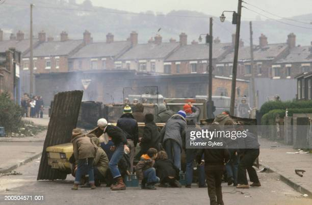 Catholic youths hijack a car and burn it out Then create a road block they are hurling petrol bombs and missiles at British Army soldiers The Troubles