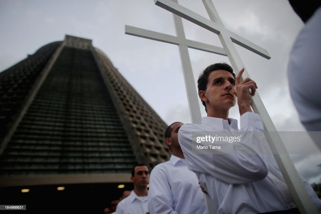 Catholics carry crosses in a Good Friday procession following Mass at the Metropolitan Cathedral on March 29, 2013 in Rio de Janeiro, Brazil. The conical shaped cathedral can accomodate 20,000 worshippers. Pope Francis is the first pope to hail from South America, with Brazilian Catholics set to receive the pontiff during his visit to Brazil in July for a Catholic youth festival. Brazil has more Catholics than any other country.