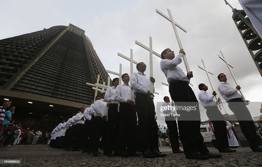 Catholics carry crosses in a Good Friday procession following Mass at the Metropolitan Cathedral (L) on March 29, 2013 in Rio de Janeiro, Brazil. The conical shaped cathedral can accomodate 20,000 worshippers. Pope Francis is the first pope to hail from South America, with Brazilian Catholics set to receive the pontiff during his visit to Brazil in July for a Catholic youth festival. Brazil has more Catholics than any other country.