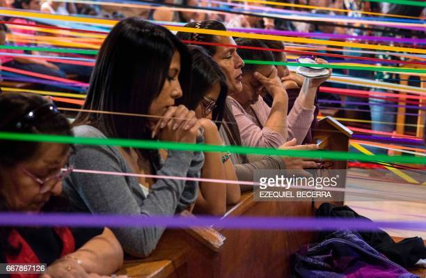Catholics hold colored tape tied to a statue of Jesus Nazareno while attending a mass at the San Antonio de Padua church before a procession known as...